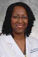 A smiling woman with curly hair wearing glasses and a white lab coat.