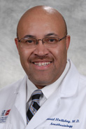 A smiling man wearing glasses and a white lab coat.