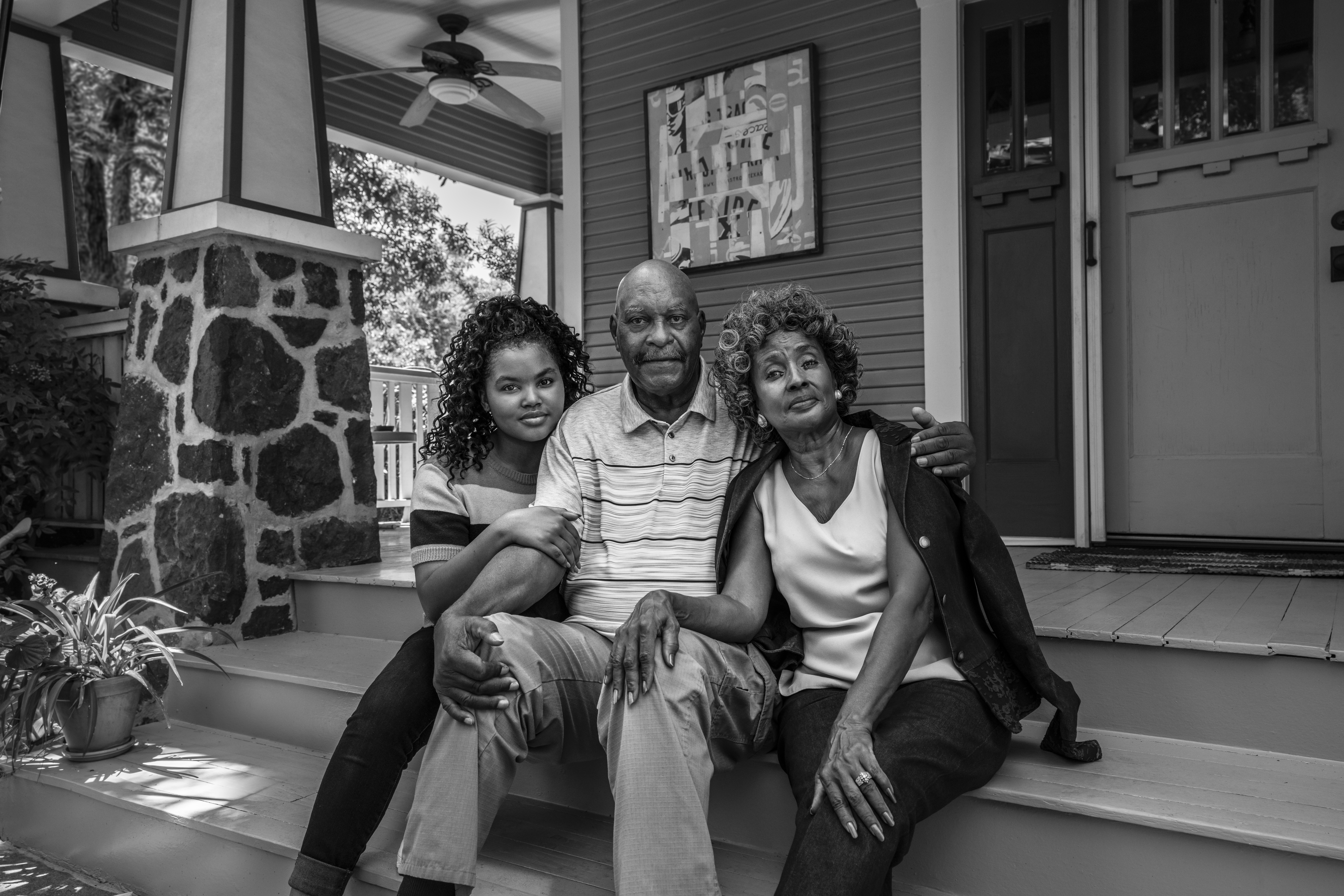 Two elders and a young woman sitting on the steps in front of a house.